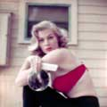 Anita Ekberg is photographed by Milton H. Greene outside in LA for Look Magazine in 1954. Annita is faced to the side sitting wearing a red velour bra and black leggings holding a comb and mirror looking lovely towards the camera.