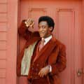 Decked out head to toe in a brown corduroy suit while holding a cigar and leaning against a door, Bill Cosby can be seen with his trademark pursed lips and smirk. This classic image of Cosby was taken by Milton H Greene in Hollywood in 1969.