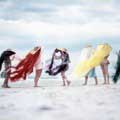 On assignment for Look Magazine in 1956, Milton H Greene snapped this fun, color photograph of six models on Jones Beach, New York each wearing beach hats with flowing grass of different colors covering their faces except the model on the far right. The model on the far right is wearing a blue pant suit and is the only face seen.The rest of the models are wearing 50's era beach-ware, swimsuits, bathing suits.