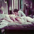 Marilyn Monroe is Cherie in this image from her classic 1956 movie Bus Stop. Here Marilyn is laying in bed, looking up at her co-star Don Murray, who has his arm on her shoulder. Milton H Greene took this on location color photograph.