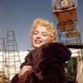 Color photo of Marilyn Monroe taken by Milton H. Greene on the set of the movie Bus Stop in Tahoe in 1956. Marilyn is smiling at the camera wearing a dark fur coat wrapped around her with rustic scaffolding in the background.