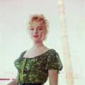 In this 1956 photograph taken on the set of Bus Stop by Milton H Greene, Marilyn Monroe is looking directly at the camera wearing red lipstick. Marilyn is wearing a green blouse in this on location image.