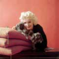 While on an editorial shoot for Look Magazine in 1955, Milton H. Greene took this classic shot of Marilyn Monroe with two Pekingese dogs. Marilyn has her head nestled next to a dog laying on a stack of red pillows as she smiles directly into the camera.