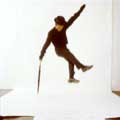 A jumping Sammy Davis Jr. is wearing a black hat and a black outfit against a white background. His left arm is holding an umbrella while his right arm is reaching up. Milton H. Green took this classic image.