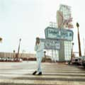 Sammy Davis Jr. is seen in all his King of Cool glory in this classic 1967 photograph by Milton H. Greene. Taken in front of the original Sands Casino sign in Las Vegas, Sammy is wearing a white corduroy suit and red turtleneck sweater and black boots. This image has been used many times on Sammy album covers as well as version on comedian Chris Rock DVD.